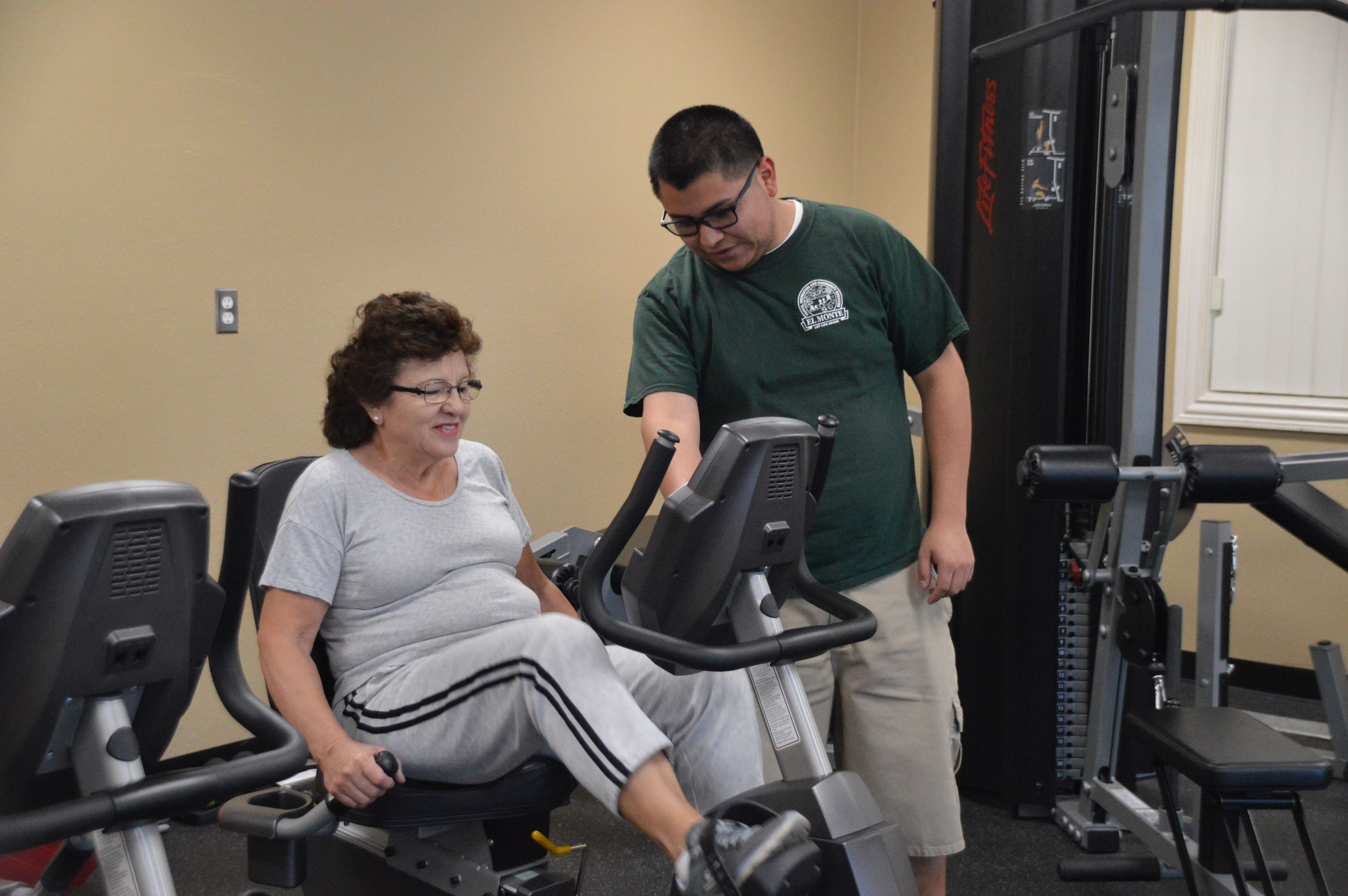 Staff assisting woman on the machine at the senior gym