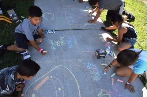 close up of children drawing with chalk