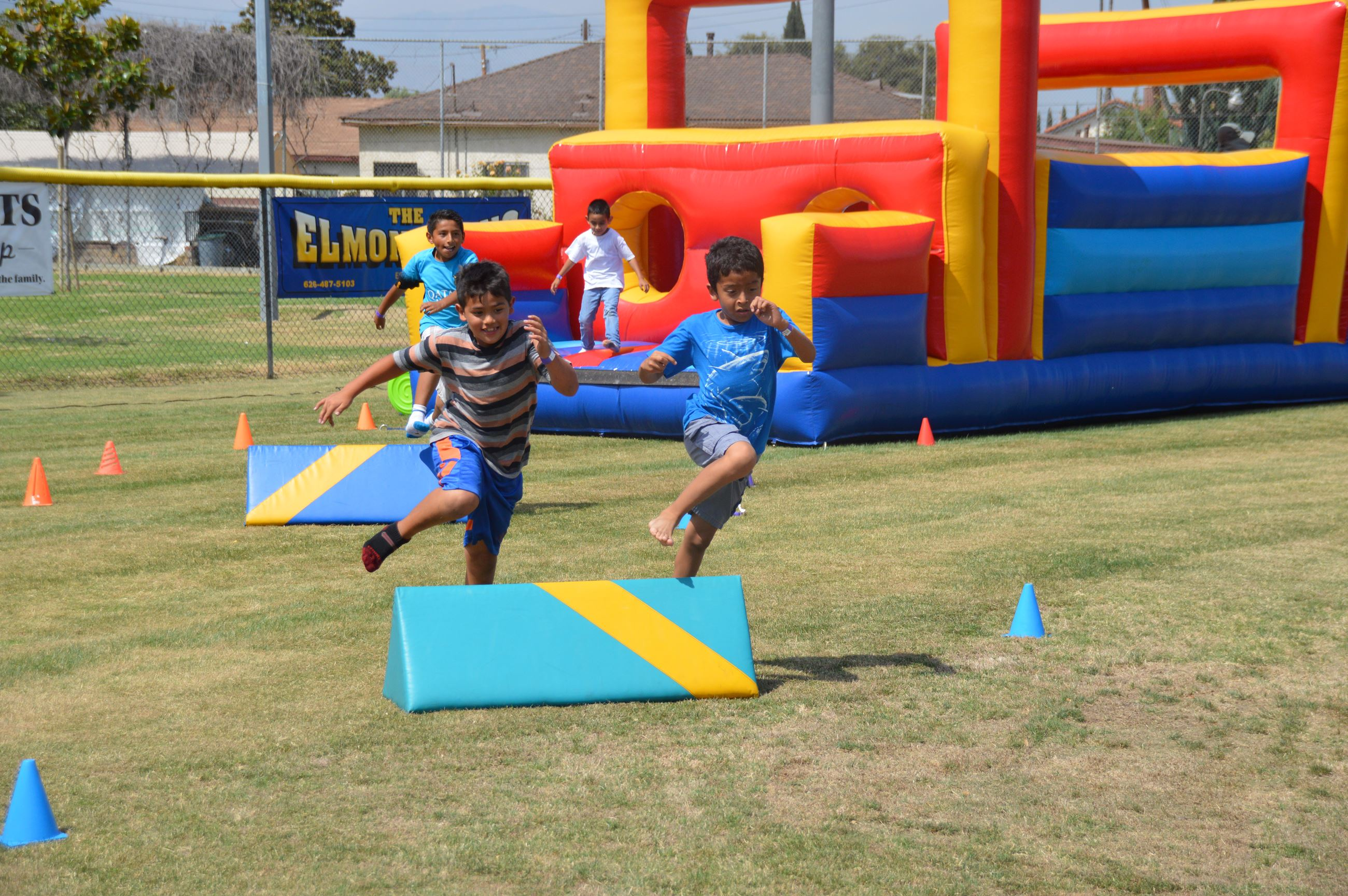 Two kids jumping over an obstacle at the Red, White and Bounce! Health & Wellness Fair