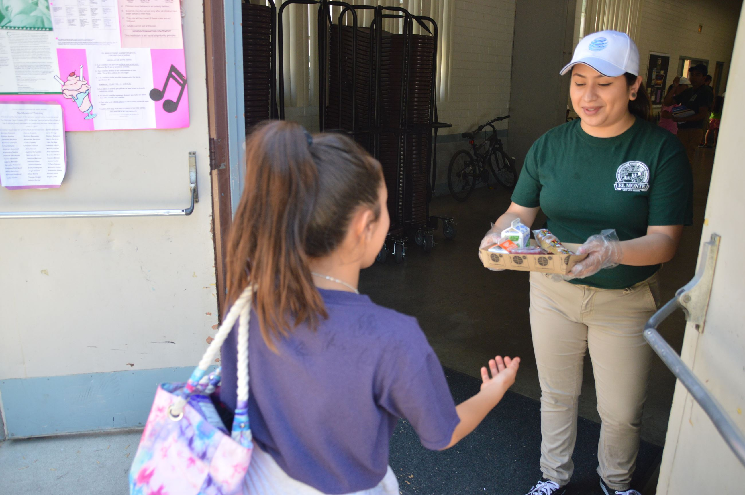 Park leader handing out a meal to a child during the Summer Food Program