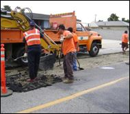 people in orange working on a road