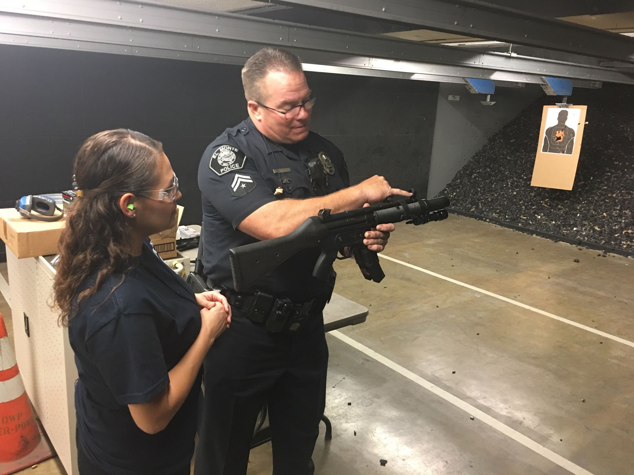Officer Showing Woman a Part of a Gun at Shooting Target Space